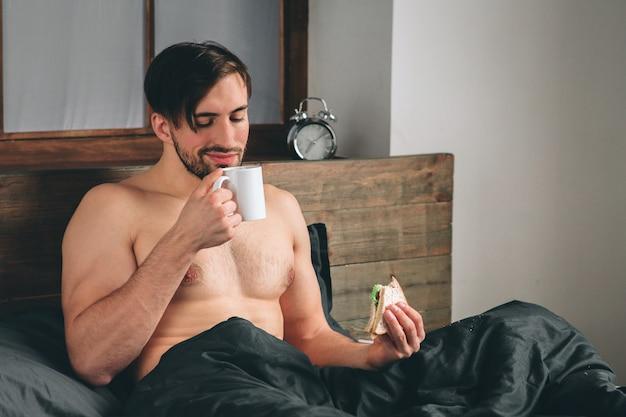 Красивый улыбающийся молодой голый мужчина держит чашку кофе и смотрит в сторону, сидя на кровати