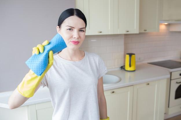 Яркая и красивая брюнетка стоит и позирует. она держит синюю тряпку в руках, покрытых желтыми перчатками. девушка смотрит на камеру. она серьезная