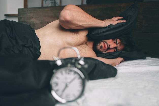 起きる時間。幸せではないベッドで疲れた男。仕事の時間を確認しながら目覚まし時計を保持している成熟した男