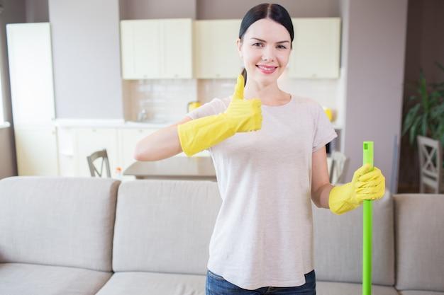 Девушка стоит в квартире и показывает большой палец вверх. женщина носит желтые перчатки и держит зеленую палку левой рукой. она позитивна.