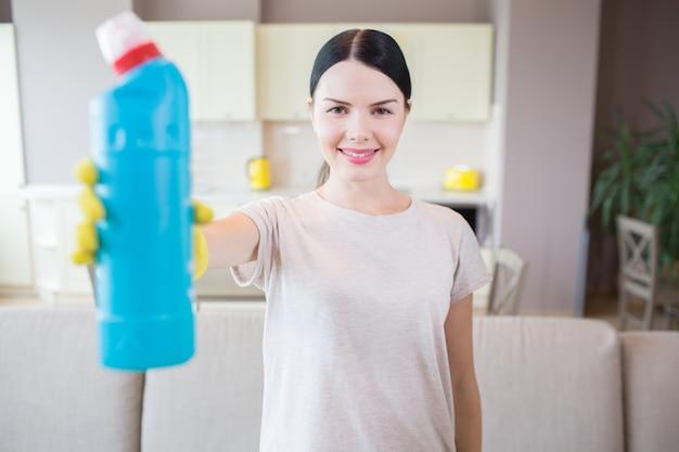 Брюнетка стоит и показывает бутылку с синей жидкостью. женщина смотрит на камеру и улыбается. она в середине комнаты.
