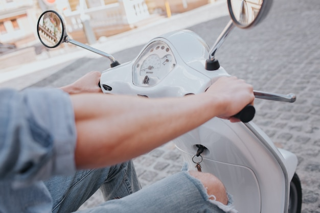 Уверенный и привлекательный молодой человек сидит на мотоцикле