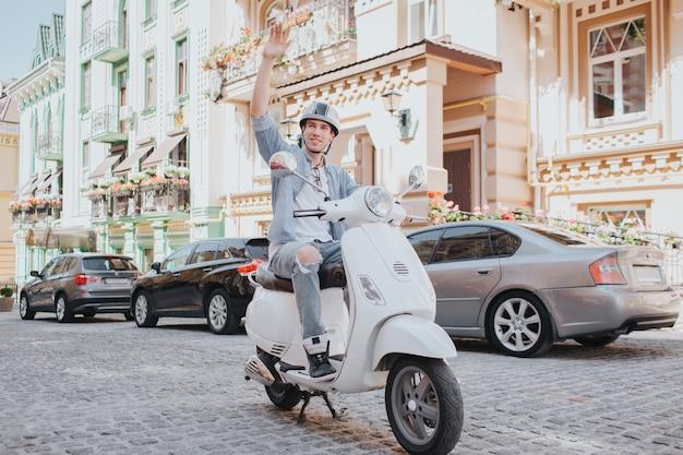 カジュアルな服装の男はバイクに乗っています。