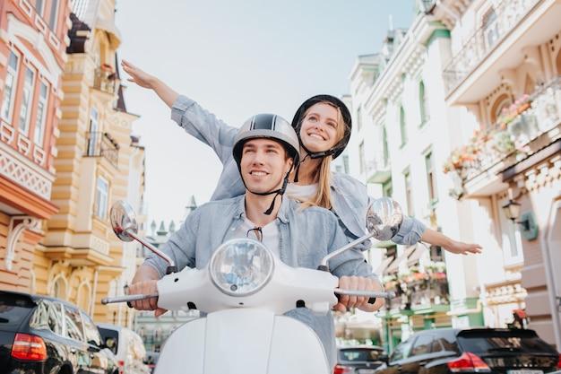 幸せなカップルはバイクに乗っています。