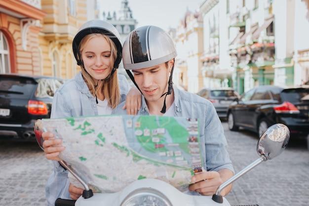 市内でバイクに乗って地図を見る豪華なカップル
