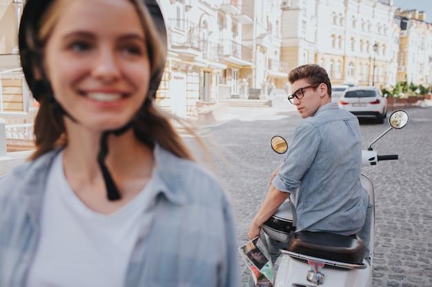Красивая и привлекательная женщина стоит, а парень сидит на мотоцикле сзади и смотрит на нее