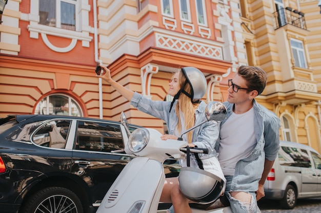 Блондинка сидит на велосипеде со своим парнем и принимает селфи