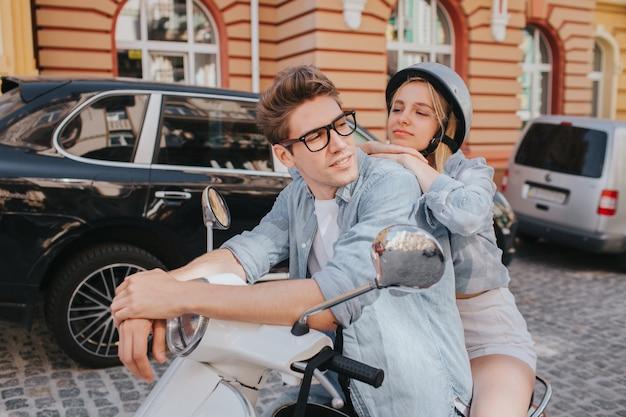 Утомленная женщина сидит позади своего парня на мотоцикле и наклоняется к нему.
