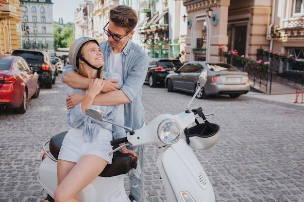 素敵なカップルが一緒にモーターサイクルに座っています。