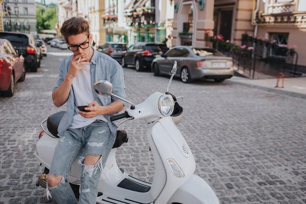 Красивый парень сидит на мотоцикле и держит телефон в руке