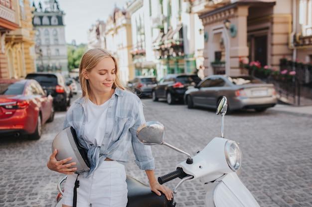 Прекрасная женщина сидит на мотоцикле и смотрит на него