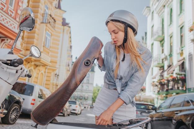 Шикарная и симпатичная женщина смотрит под сиденье мотоцикла
