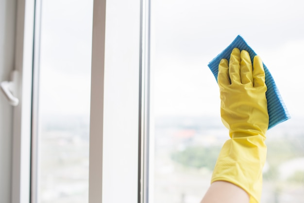 窓のガラスを掃除する黄色い手袋で人間の手。青い布でこれを行います。外の日です。