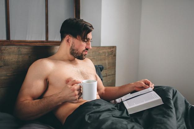 彼の寝室にいる熱いお茶やコーヒーを保持しながらエキサイティングな本を読んでハンサムな男。朝の時間です。より近いビュー