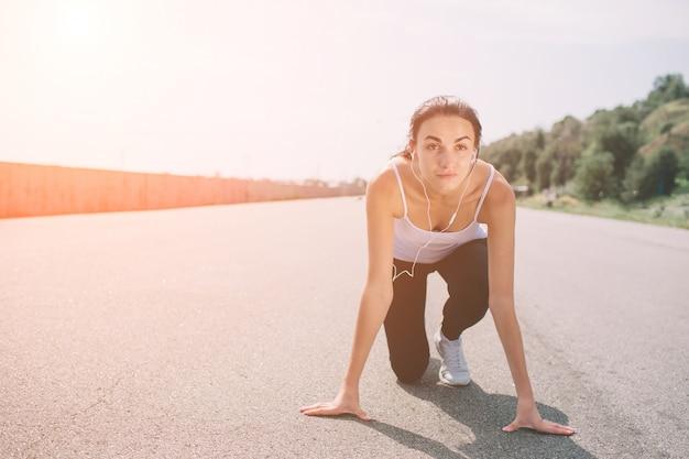 Молодая женщина спортсмен в исходное положение готов начать гонку. женский спринтер готов к спортивным упражнениям на беговой дорожке с солнечной вспышкой