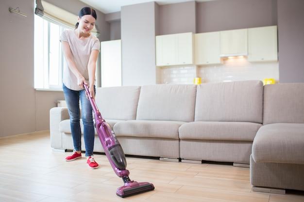 女性はワンルームマンションに立って、床を掃除します。彼女はそのために掃除機を使用しています。女の子が見下ろしています。