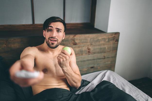 ベッドで横になっているテレビを見ている裸のひげを生やした黒髪