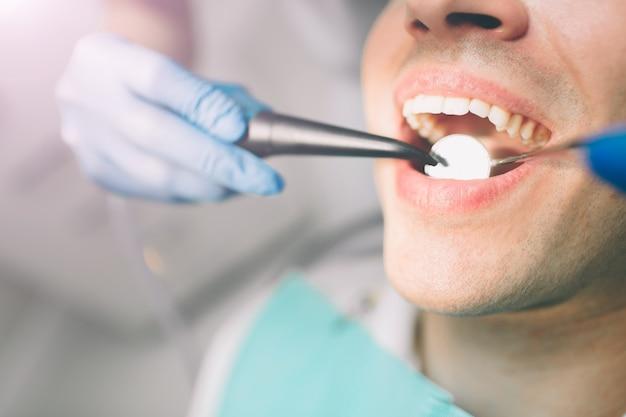 若い患者の歯を治療する歯科医の肖像画。