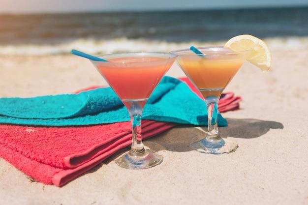 Летняя концепция: свежий экзотический коктейль на песчаном пляже. красочные полотенца лежали рядом. это на берегу моря. рай.
