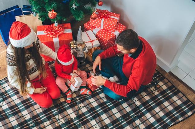 Веселого рождества и счастливого нового года. малыш сидит между родителями и открывает подарок. она сосредоточена. парень держит красный фонарь и смотрит вниз. мать сидит и смотрит на ребенка. она носит новогоднюю шапку.