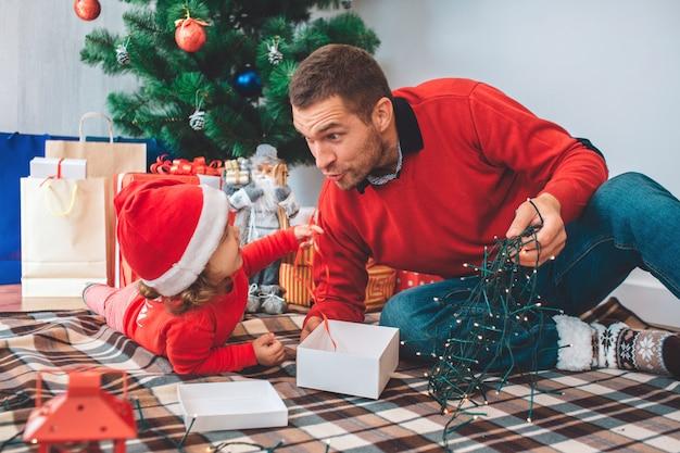 メリークリスマス、そしてハッピーニューイヤー。毛布の上に親子の素敵な写真。女の子は胃に横たわっています。男は子供を見て、クリスマスライトを保持します。彼らは一緒に座っています。