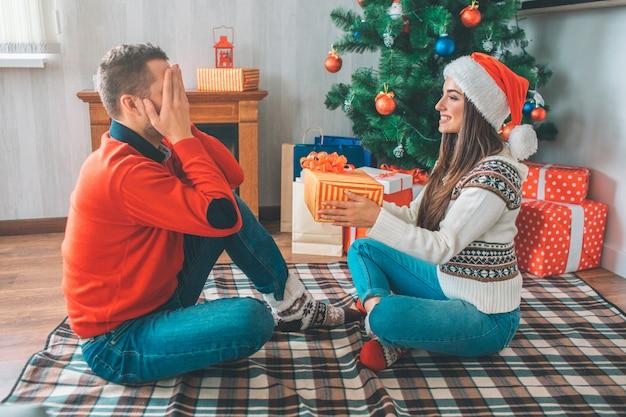 Изображение человека, сидящего перед женщиной и держит глаза закрытыми. она держит подарок для него.
