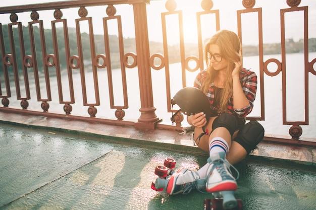 スリムでセクシーな若い女性とローラースケート。市内の夏のアクティブな休暇。エクストリームスポーツ
