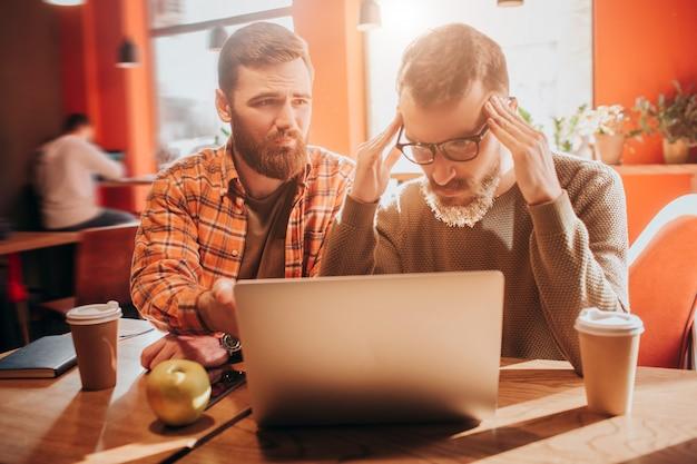 Один из парней расстроен и смотрит на экран ноутбука, а другой с надеждой и грустью смотрит на своего друга.