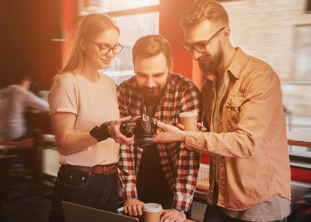 Красивая блондинка девушка стоит возле молодых и бородатых парней в маленьком кафе и показывает им фотографии на камеру. мужчины довольны результатом фотосессии.