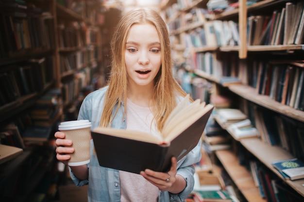 本を読んで、コーヒーを飲む女の子のクローズアップ。この本はとても面白いので、読むのをやめられません。少女は研究室に立っています。