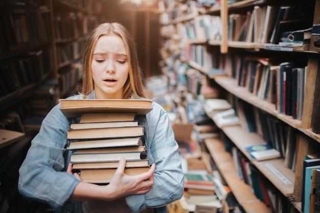 女の子はたくさんの本を手に持っています。彼女にとっては難しい。彼女は無力で疲れているように見えます。女の子は大きな古い図書館に立っています。