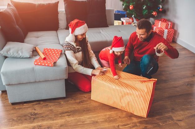 メリークリスマス、そしてハッピーニューイヤー。ギフト用の紙を保持している小さなヘルパーの写真。彼女の両親は微笑む。若い男はテープを保持し、プレゼントの表紙に使用します。女性は彼らを助けます。
