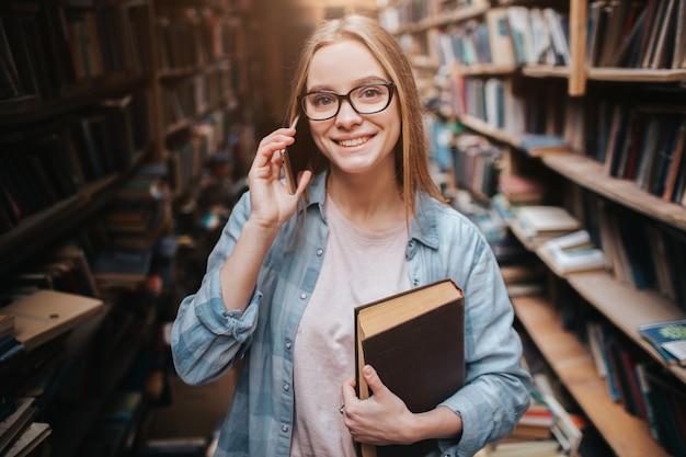 本で彼女の左手に立っていると電話で話している魅力的な女の子。彼女はまっすぐ前を見て笑っています。この女性はとてもいいです。