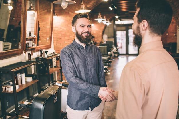 Парень в синей рубашке пожимает руку посетителю парикмахерской. ему нравилось работать с этим клиентом.