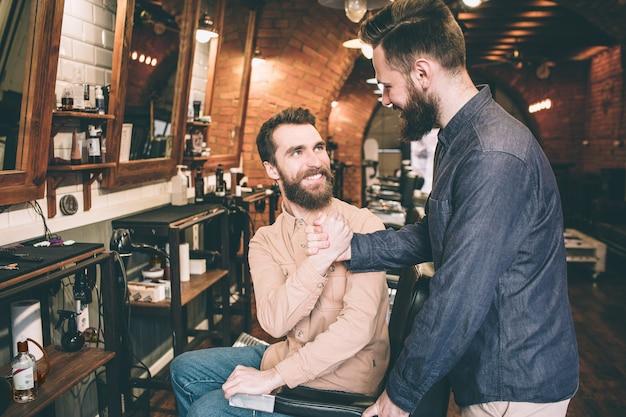 Два парня пожимают друг другу руки. тей рады встретиться в парикмахерской.