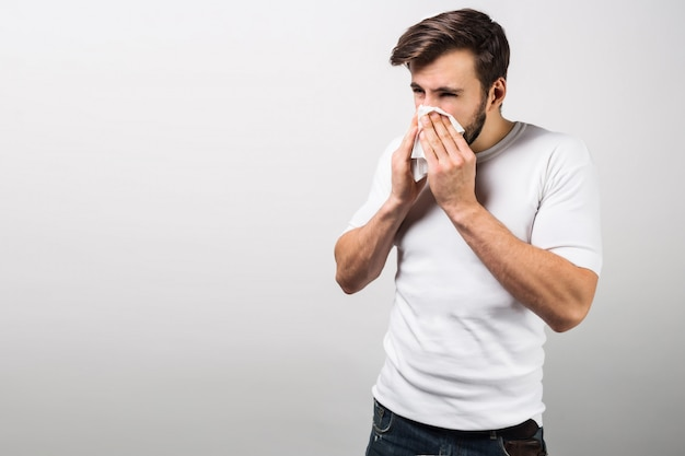 Красивый мужчина стоит возле белой стены и чихание. похоже, он простудился и скоро будет очень болен. ему нужно принять лекарство.