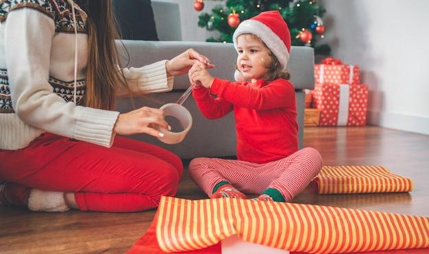 メリークリスマス、そしてハッピーニューイヤー。少女と若い女性が床に座っています。子供がテープに手を伸ばして触れます。女性はそれの残りを保持します。子供は興奮しています。彼らは愛する人へのプレゼントを準備します。