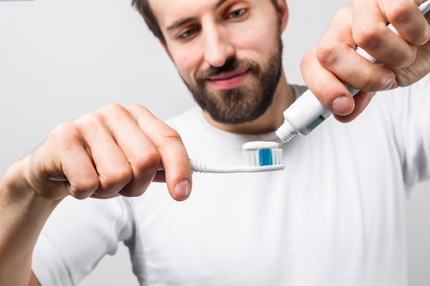 Отрежьте взгляд человека кладя некоторую зубную пасту на зубную щетку. он хочет почистить зубы. парень выглядит счастливым и довольным. закройте изолированные на белой стене.