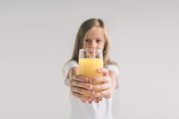 オレンジジュースのガラスを保持している幸せな女の子