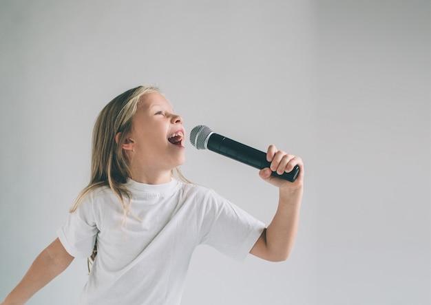 ロッキングアウトの女の子。マイクに向かって歌っている子供の画像