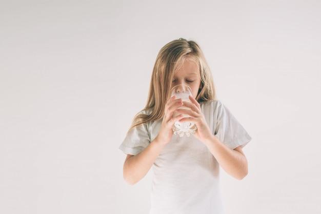 女の子はミルクの新鮮なガラスを飲んでいます。