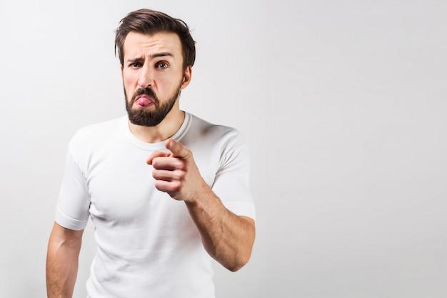 白いシャツを着た真面目な男がフレームの左側に立ってまっすぐ前を向いています。彼の顔には奇妙な感情が表れています。ビューをカットします。白い壁に分離