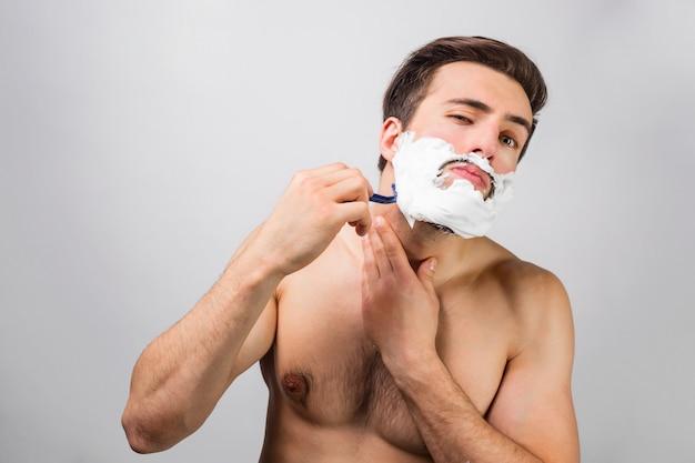 ハンサムで魅力的な男性は、彼のひげを剃る過程にあります。彼はそれについて後悔していません。この男は本当に良い刃を使用しています。広告のコンセプト。ビューをカットします。白い壁に分離