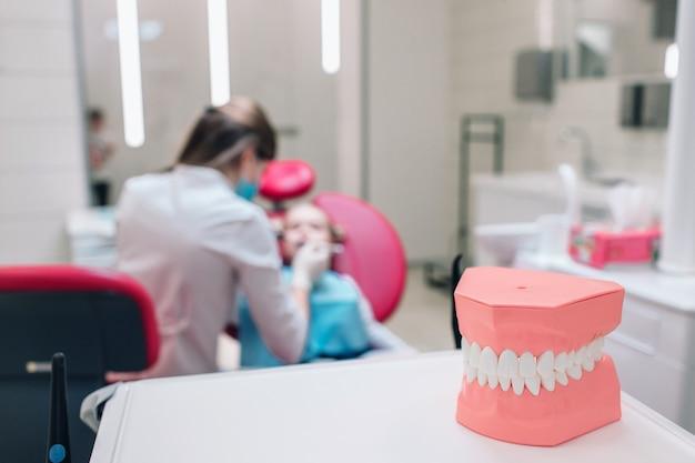 歯科医院における歯科、歯科用器具の医療機器、歯科用器具、歯科用機器。女性の歯科医と子供は壁にぼかします。