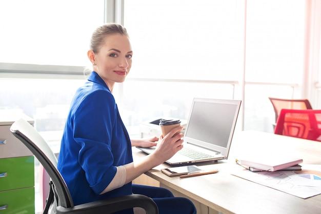 素敵できれいなビジネスの女性はオフィスのテーブルに座っています。