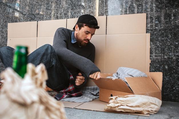 Бездомный мужчина сидит и прислоняется к стене картоном