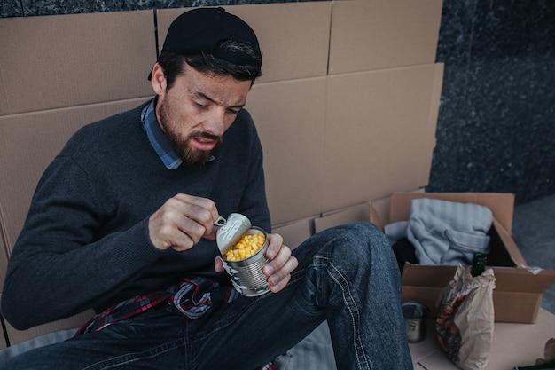 Бедный и бесчеловечный человек сидит на картоне и открывает банку с кукурузой