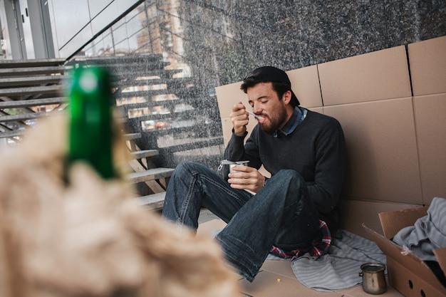 Бездомный человек сидит на картоне и ест еду из банки