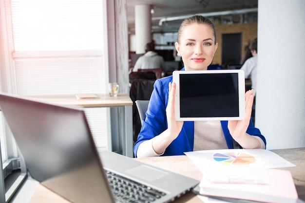 幸せなビジネスの女性は、タブレットを保持しています。