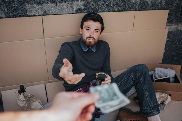 Усталый нищий сидит на картоне и смотрит на руку, которая дает ему деньги